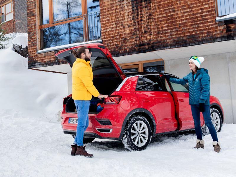 Ein Mann und eine Frau stehen im Winter an ihrem roten VW T-Roc mit VW Winterreifen