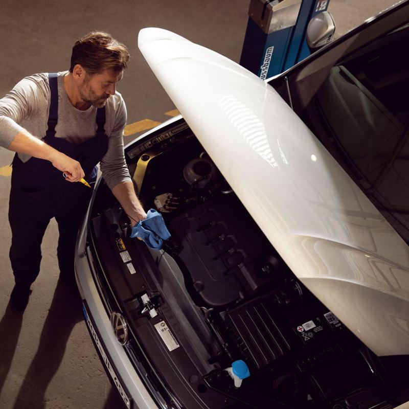 Meccanico VW Service controlla livello olio motore in un auto VW