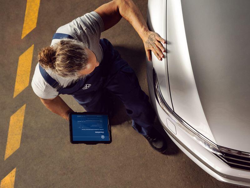 Ein VW Servicemitarbeiter prüft einen Volkswagen Auto in einer Werkstatt