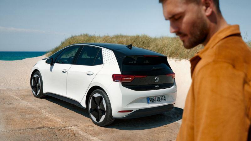 Hombre mirando al suelo con un Volkswagen ID.3 blanco de fondo aparcado en la playa