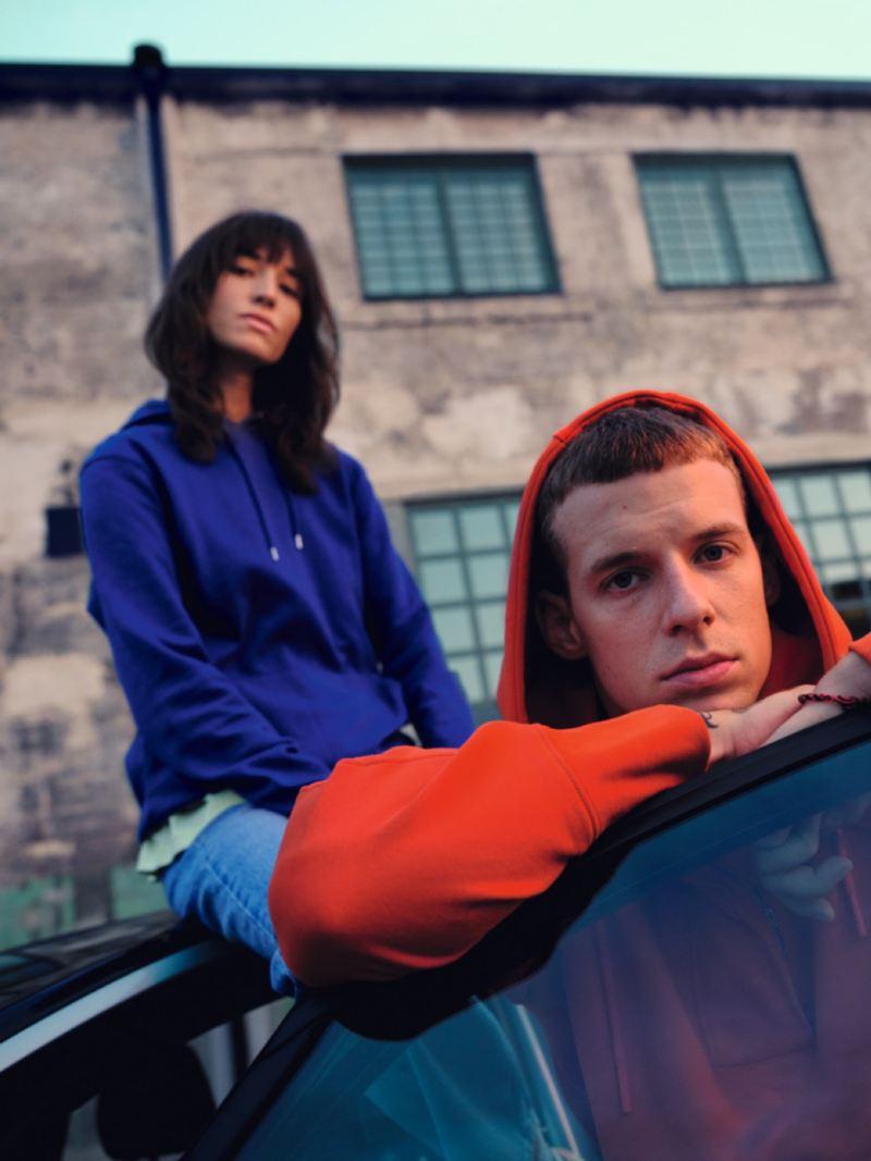 Chico con una sudadera con la capucha puesta apoyado en un Volkswagen ID.3 con una chica de fondo