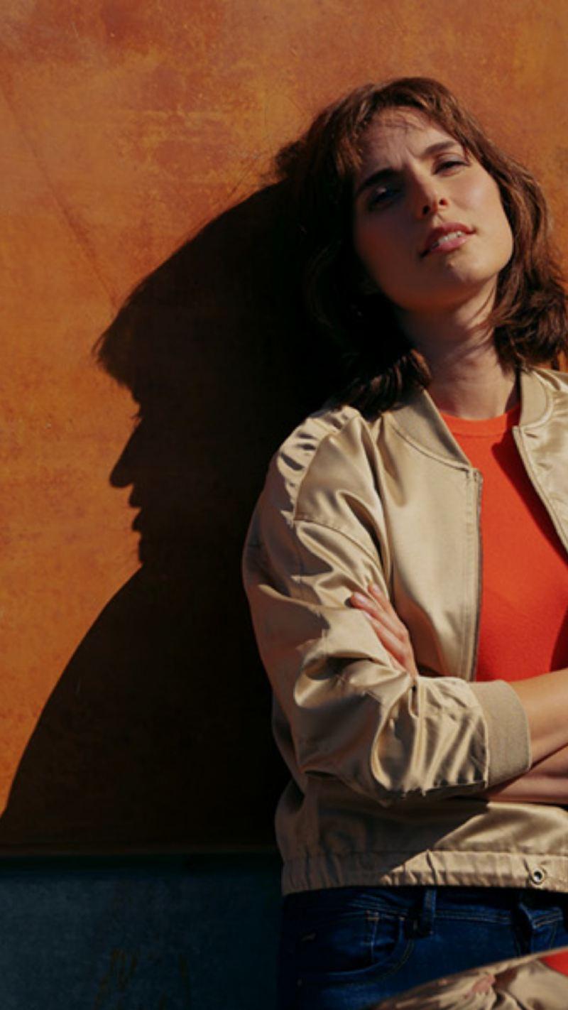 Chica con los brazos cruzados mirando a la cámara apoyada sobre una pared ocre con un ID.Charger de Volkswagen