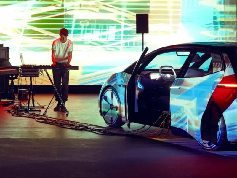 Artista Bercubs realizando una sesión en un espacio cerrado junto a un Volkswagen ID. Neo