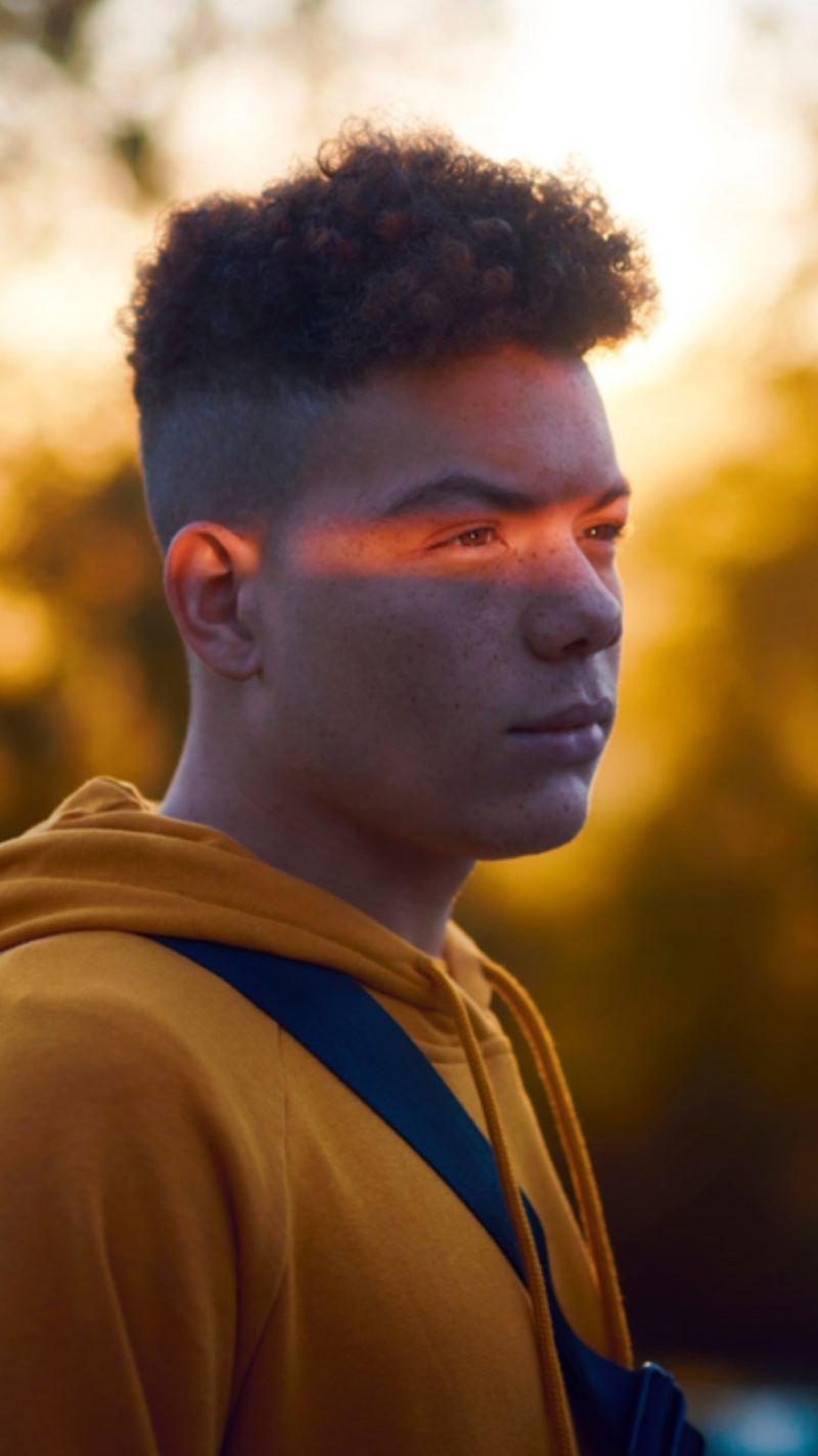 Chico en la naturaleza con una sudadera amarilla y un destello de luz en la cara