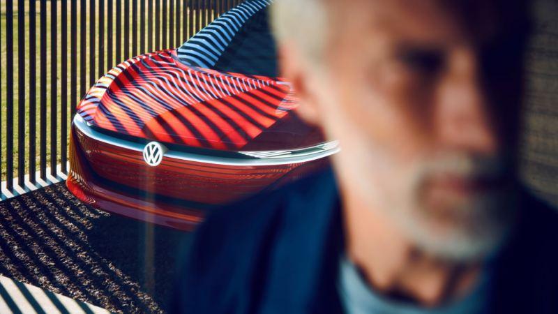 Detalle del frontal del Volkswagen ID. Vizzion rojo con sombras y reflejos de líneas