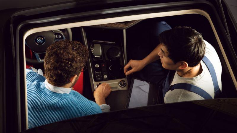 Mecánico de Volkswagen hablando con un cliente sentados en los asientos delanteros de un Volkswagen