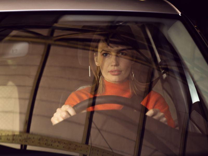 Vista frontal de una mujer conduciendo con la mirada al frente al volante de un Volkswagen