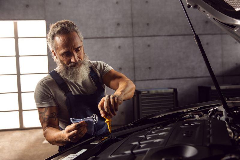 Mecánico de Volkswagen desatornillando un tornillo con el capó abierto de un Volkswagen