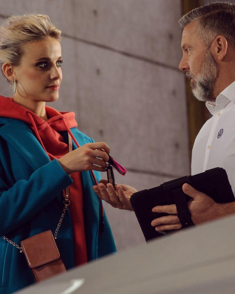 Propietaria de un vehículo entregando las llaves a un asistente de Volkswagen