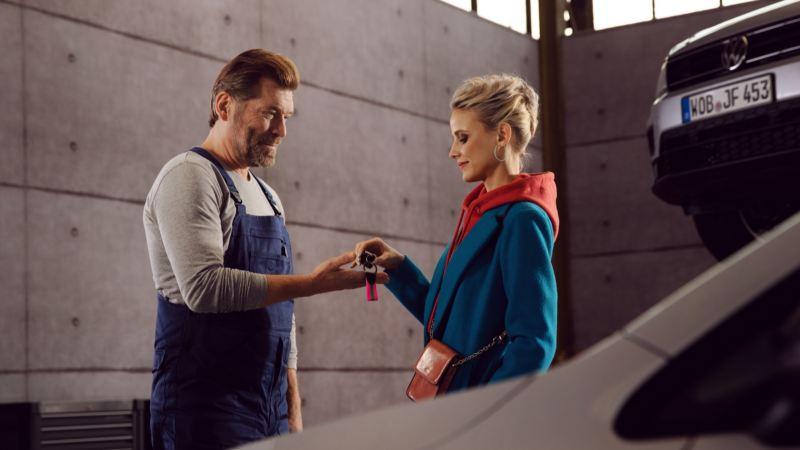 Mecánico recibiendo la llave de un Volkswagen de manos de una mujer joven