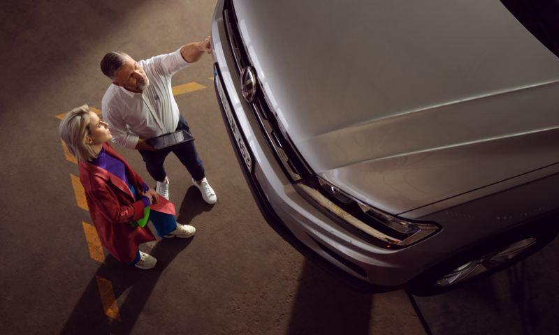 Asistente de Volkswagen hablando con un cliente frente a un vehículo elevado