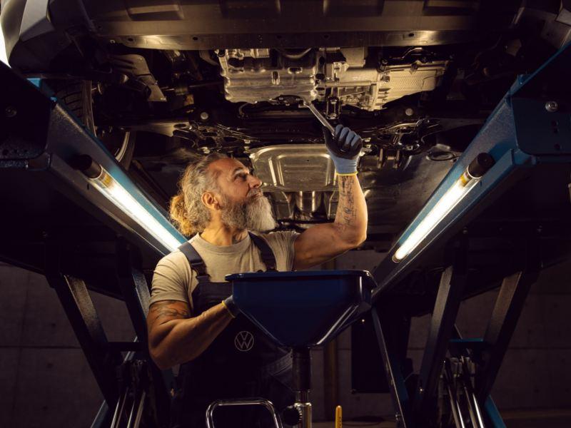 Mecánica de Volkswagen con focos de luz ajustando los bajos de un vehículo