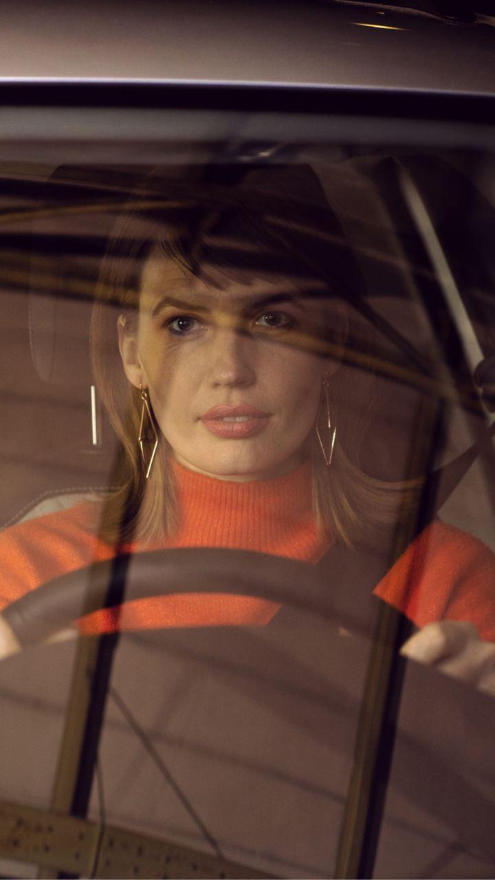 Mujer conduciendo con la mirada al frente al volante de un Volkswagen