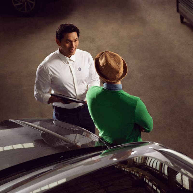 Asistente de Volkswagen hablando con un cliente apoyado sobre el capó de un Volkswagen