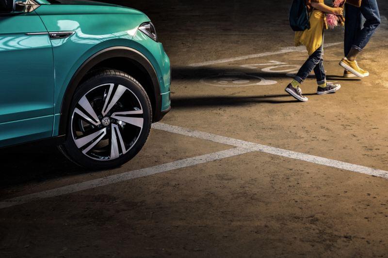 Llantas de un Volkswagen T-Cross azul turquesa aparcado tras los pies de un padre con su hija