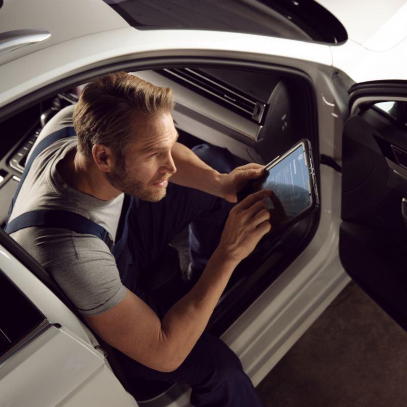 Mecánico de Volkswagen trabajando sentado en el asiento del acompañante de un vehículo
