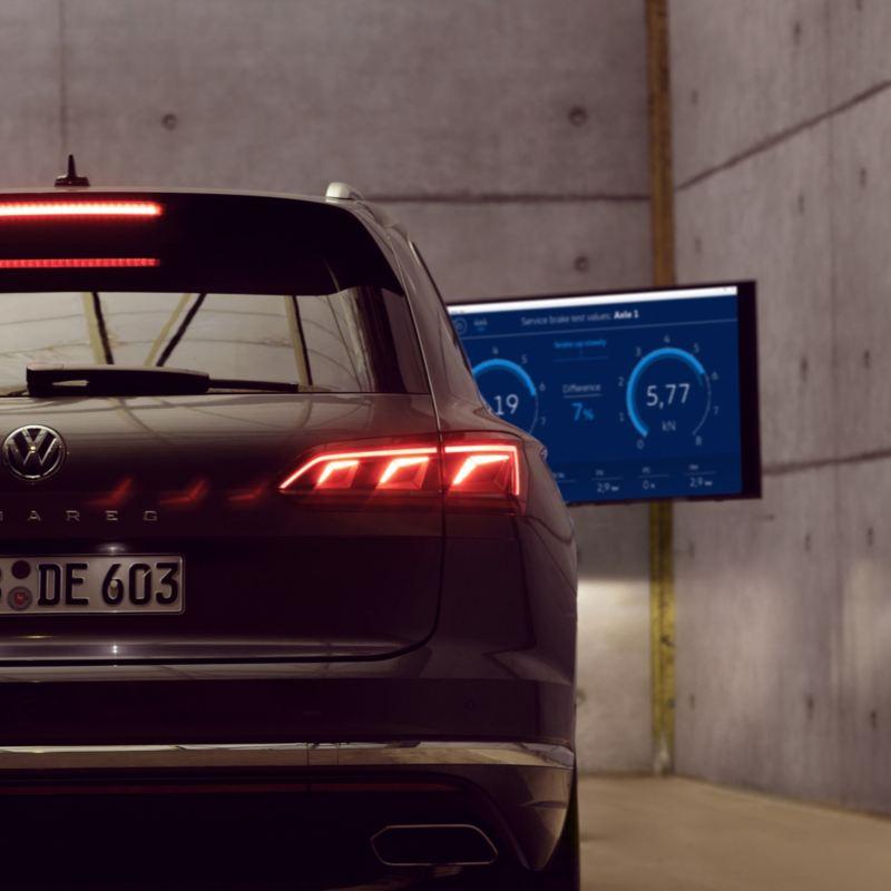 Vista trasera de un Volkswagen frente a una pantalla de comprobaciones en un taller