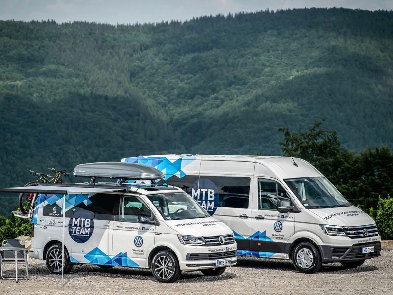 Volkswagen Crafter oraz Volkswagen California oklejone w logo MTB Team stoją na tle górzystego lasu