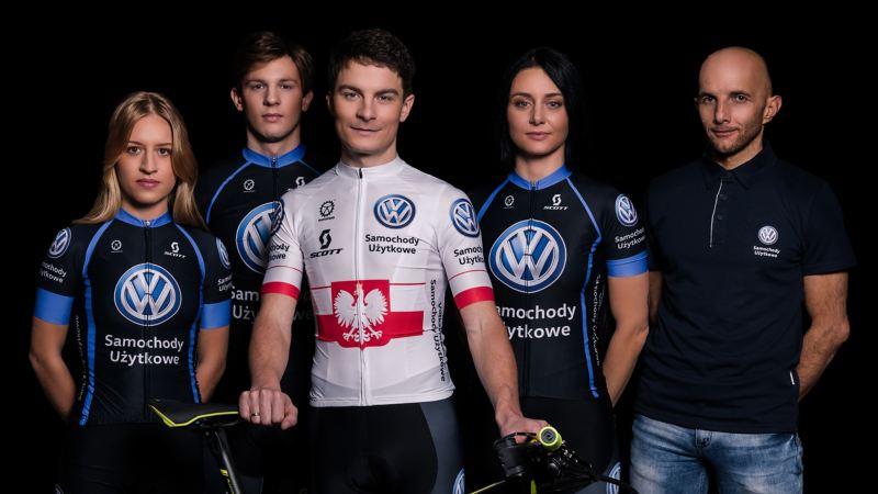 Nowy skład MTB Team stoi z rowerem na czarnym tle