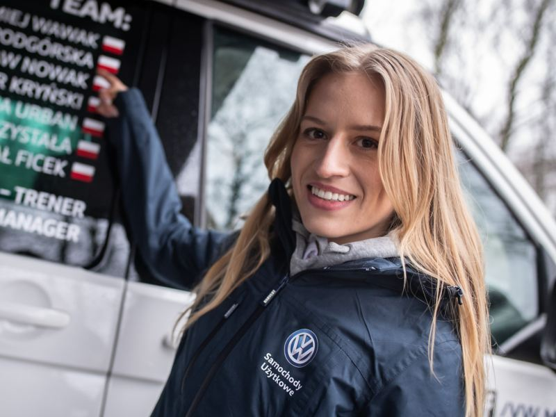 Aleksandra Podgórska stoi przed autem MTB i pokazuje swoje nazwisko na okleinie samochodu