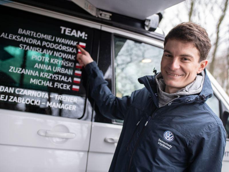 Bartłomiej Wawak stoi przed autem MTB i pokazuje swoje nazwisko na okleinie samochodu