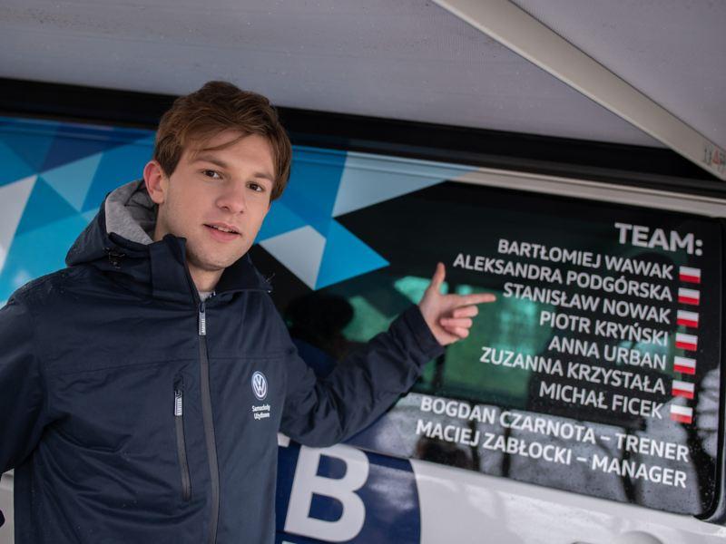 Stanisław Nowak stoi przed autem MTB i pokazuje swoje nazwisko na okleinie samochodu