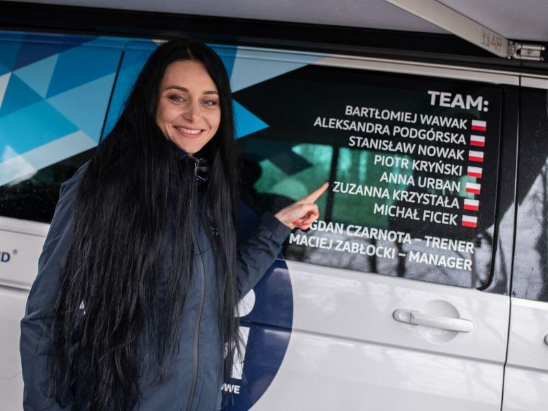 Zuzanna Krzystała stoi przed autem MTB i pokazuje swoje nazwisko na okleinie samochodu