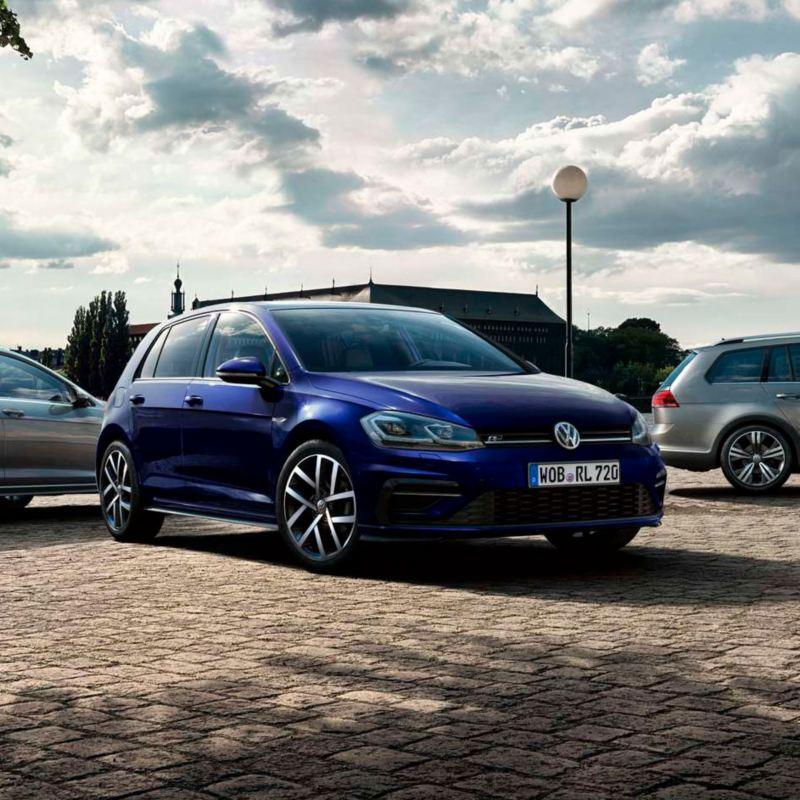 Visión frontal de un Volkswagen Golf azul en un suelo de adoquines