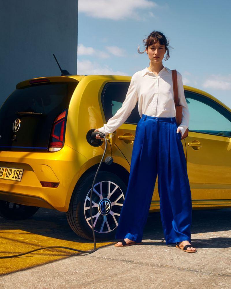 Chica mirando a la cámara mientras carga un Volkswagen e-up! amarillo en la calle