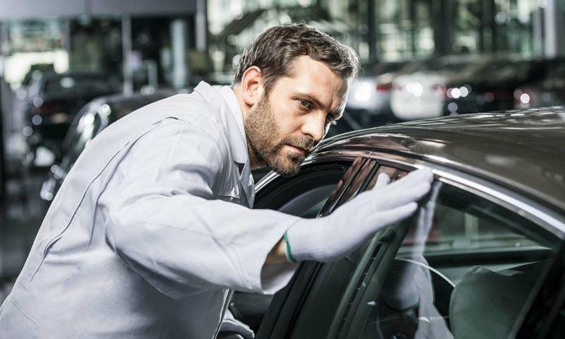 Ein Mann überprüft ein Volkswagen in der Produktionshalle