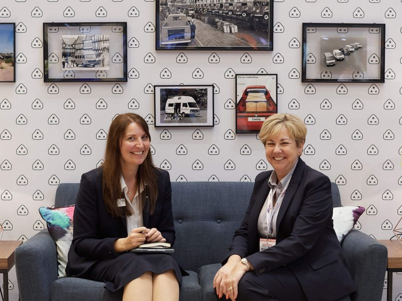 Two women smiling, sitting on a sofa inside the VW Commercial Vehicle show living room