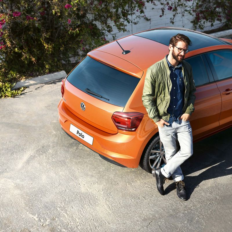 A man leaning on a Volkswagen Polo