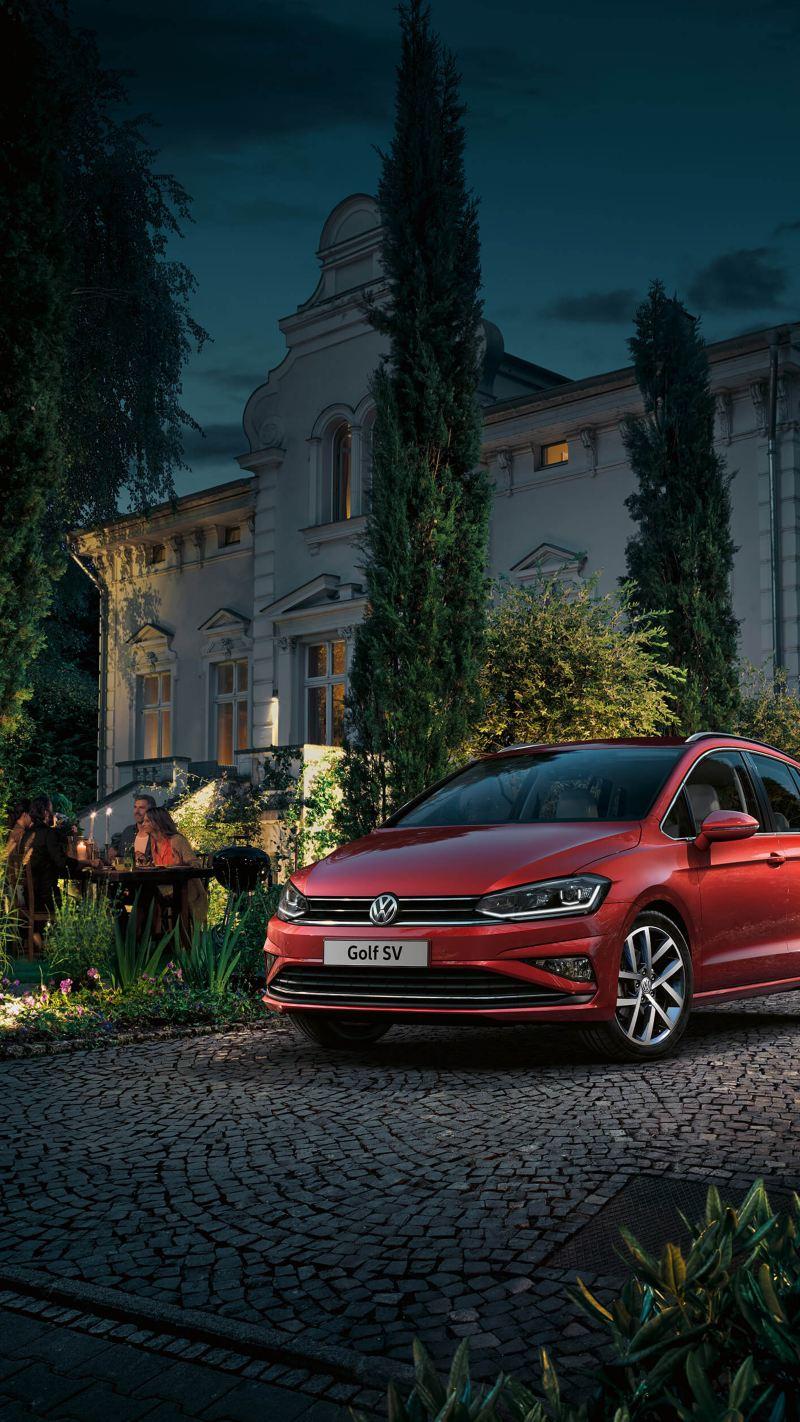 Red Volkswagen Golf SV parked outside a mansion