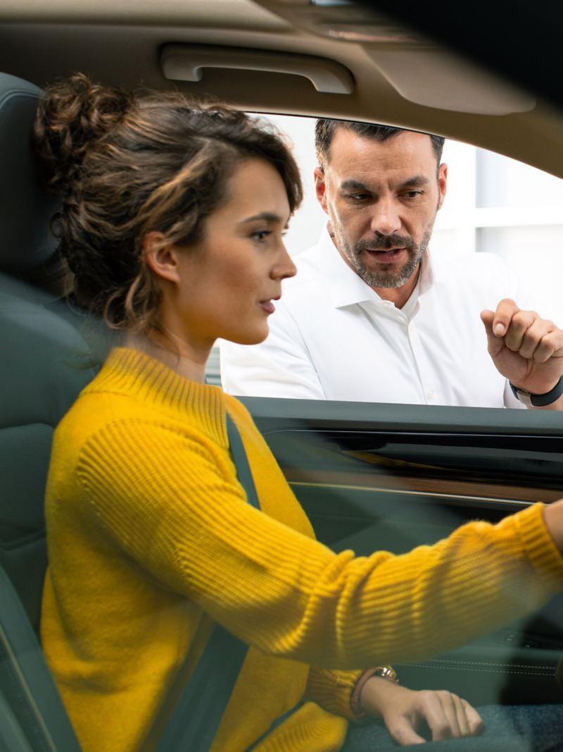 Man talking to woman in car