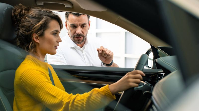 A woman in a car talking to a VW Service Manager
