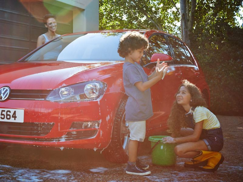 A family washing a VW Golf
