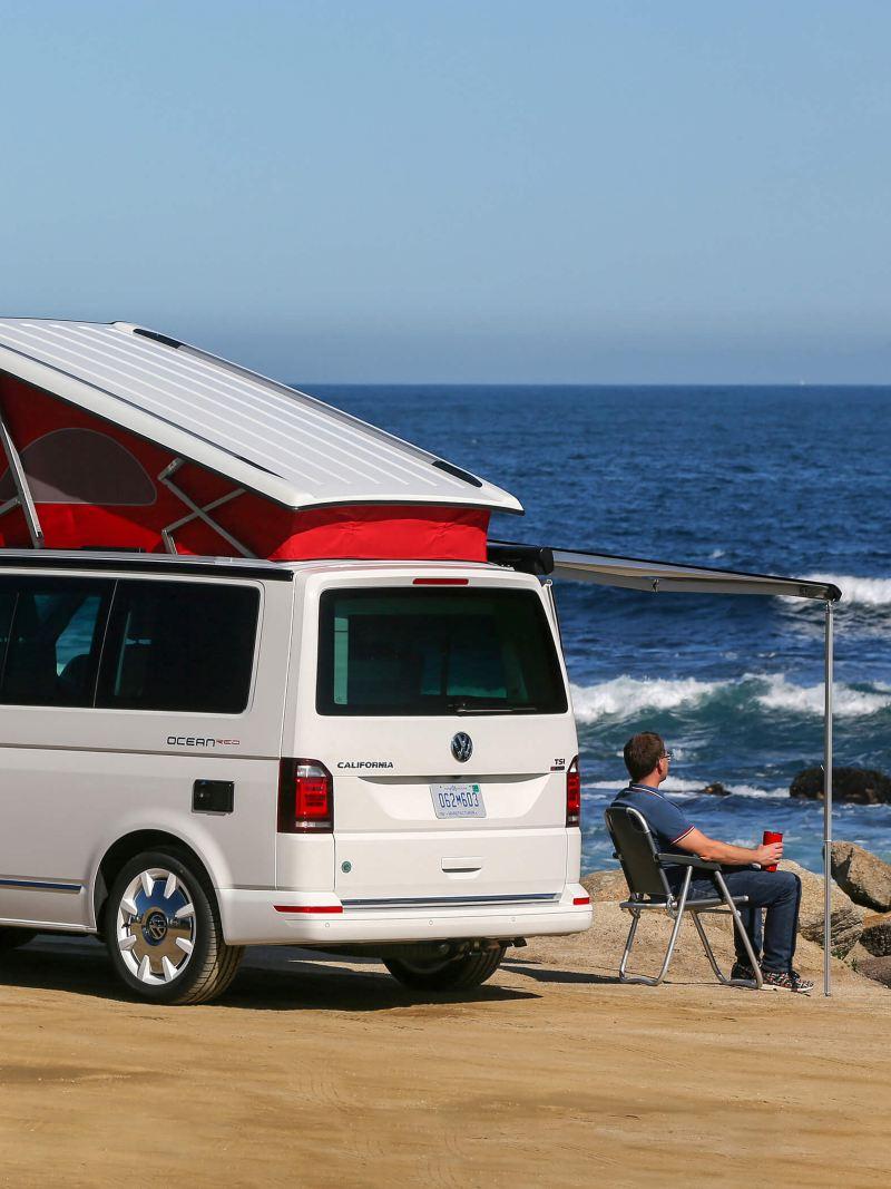 man sat outside VW California by ocean