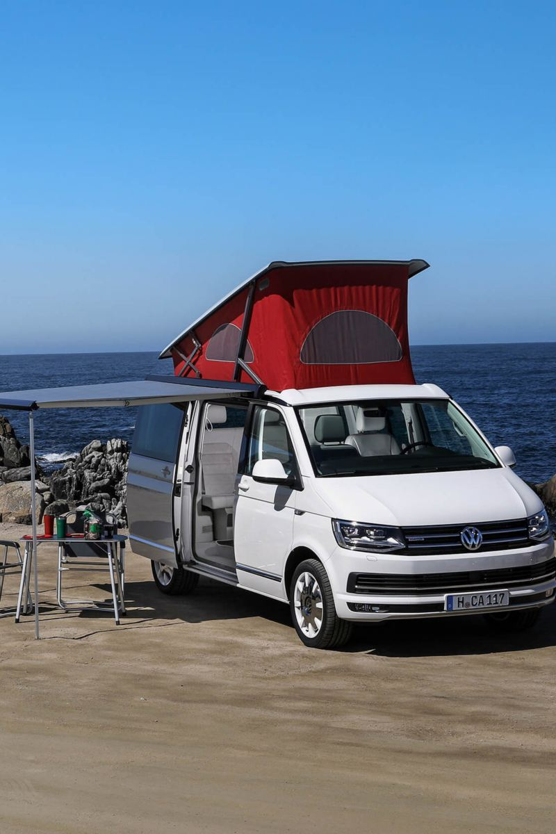 VW T3 and T6 California camper vans parked by ocean