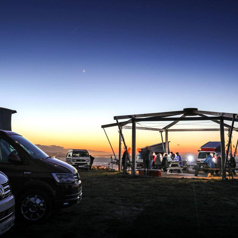 VW California vans parked on beach at sunset