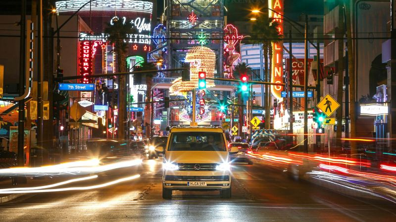 VW California driving by neon city lights at night