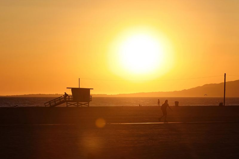 People playing on California beach at sunset