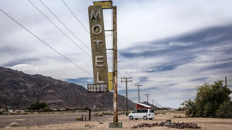 VW California parked by historic neon motel sign