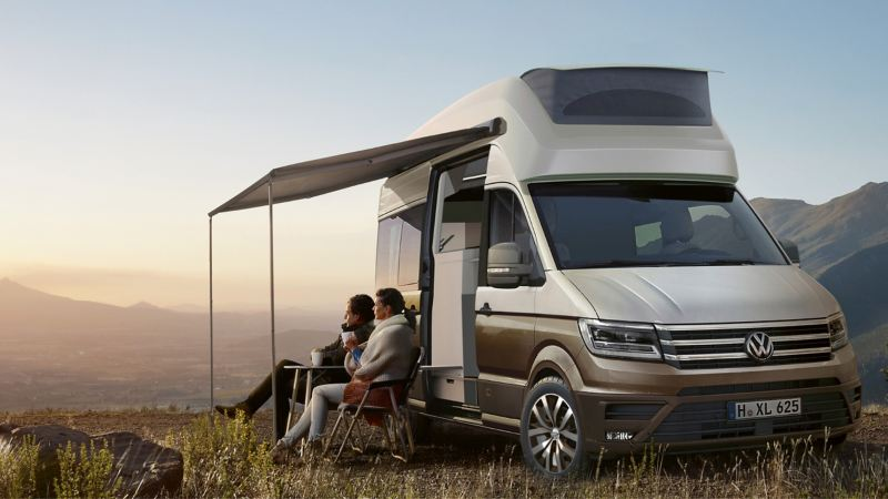 Couple sitting outside camper van
