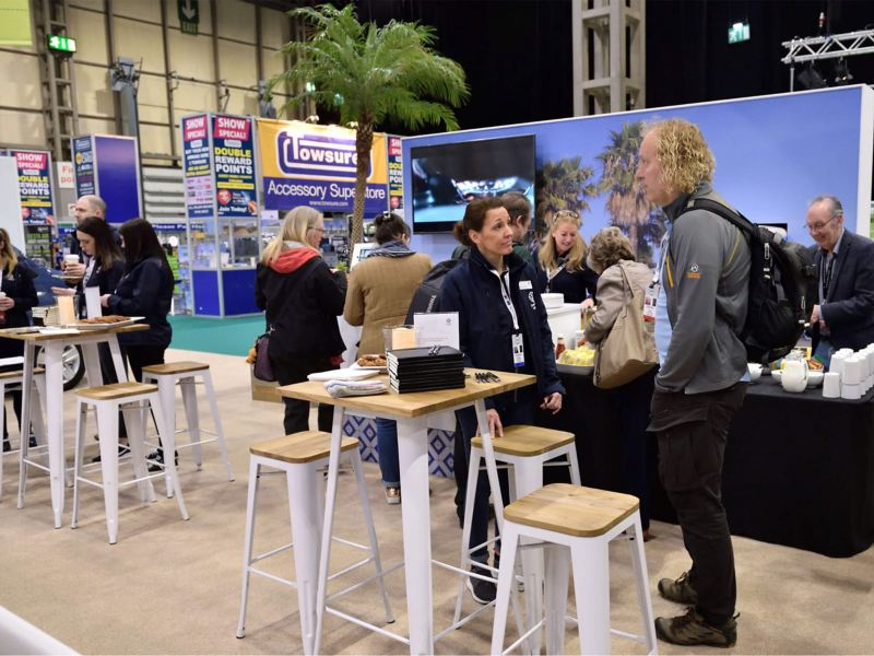 People at the Caravan, Camping & Motorhome Show 2019 with the Volkswagen beach cabana stand in background.