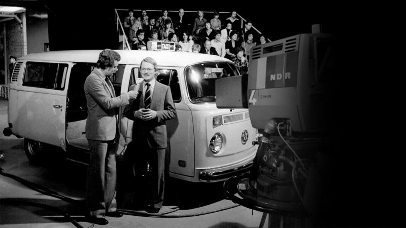 Black and white photograph of E-campervan and Adolf Kalberlah being interviewed for TV show