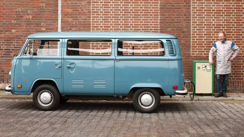 Man standing next to blue E-camper van charger
