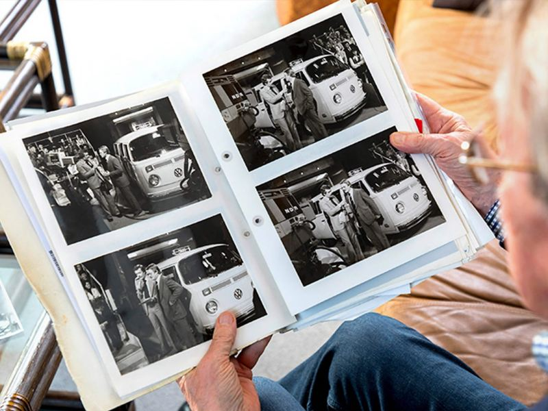 Person looking at old black and white photographs of a camper van being charged
