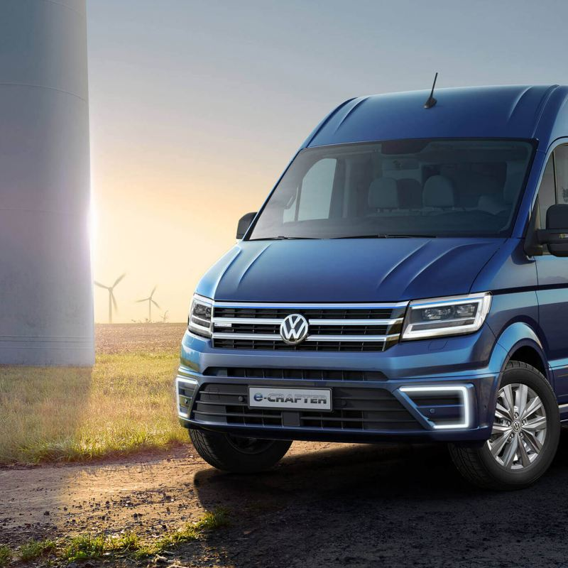 Volkswagen electronic crafter on a countryside road next to wind turbines