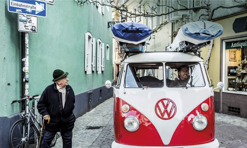 Red and white camper van on cobbled street