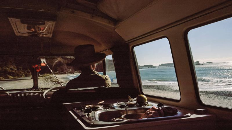 Woman sitting in camper van looking out to the beach